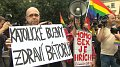 Martin C. Putna holds the sign 'Catholic queers salute Bátora', photo: Czech Television