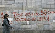 A woman walks past graffiti on a wall reading, 'We dont want what belongs to others, we won't give away Kosovo', as well as featuring the acronym of the SKOJ, the League of Socialist Youth of Yugoslavia, in Belgrade, Serbia, photo: CTK
