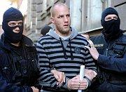 Policie přiváží jednoho ze zadržených na služebnu v pražské Bartolomějské ulici (Foto: ČTK)