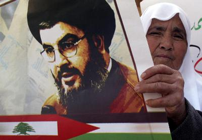 A Palestinian woman holds a poster of Sheik Hassan Nasrallah, the leader of Hezbollah, during a marc