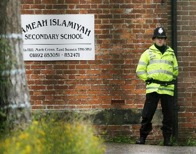 A British police officer stands guard outside Jameah Islamiyah Secondary School in Mark Cross