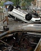 A man passes by burnt out cars in front of the Hungarian State Television building in Budapest, Hungary, on Tuesday