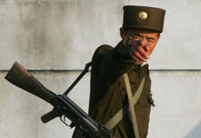 North Korean soldier reacts to a photographer on a passing boat, on the waterfront at the North Kore