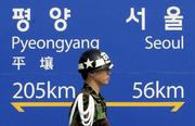 A South Korean military police walks past a signboard showing the distance to the North Korean capital Pyongyang and South Korean capital Seoul from Dorasan Station of incomplete inter-Korea railway in the demilitarized zone (AP Photo/ Lee Jin-man)