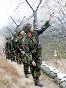 South Korean Army soldiers patrol along the barbed-wire fence in Paju, near the demilitarized zone (DMZ) of Panmunjom, South Korea, Monday, Oct. 9, 2006. South Korea's Defense Ministry said the alert level of the military had been raised in response to the claimed nuclear test.