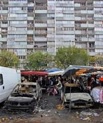 A marketplace in Clichy-sous-Bois setup next to torched cars