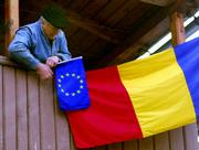 An elderly Romanian man pins the European Union flag to a Romanian flag hanging from his balcony on the outskirts of Iasi, northern Romania