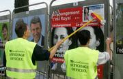 Employees of American company ClearChannel stick posters of French presidential candidates