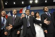 French conservative presidential candidate Nicolas Sarkozy, flanked by supporters, sings the national anthem at the end of a campaign meeting