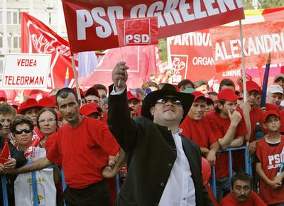 A man waves a flag during a rally by anti-Basescu parties in support of the impeachment of suspended