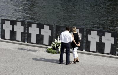 Tourists look on the remembrance crosses for the victims of the Berlin wall at the river Spree near