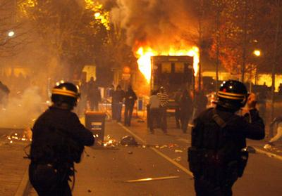 Riot police face young residents of Villiers-le-Bel, a northern Paris suburb, while a garbage truck