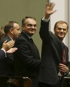 Polish Prime Minister Donald Tusk, right, waves after his speech in the parliament presenting the new government's program
