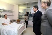 French President Nicolas Sarkozy, second right, and Interior Minister Michele Alliot-Marie, right, visit an unidentified police officer injured during clashes with rioters