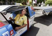 Louis Palmer of Switzerland sits inside his solar powered-car called Solar Taxi outside the venue of the U.N. climate change conference in Nusa Dua, Bali island, Indonesia