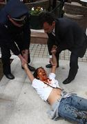 Greek Police officers attempt to arrest a pro-Tibetan protester, with red paint covering her face