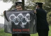 Policemen detain a protester as he holds a banner at the beginning of the flame-lighting ceremony for the Beijing 2008 games