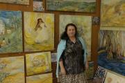 Romská malířka Mona Metbach před svými obrazy