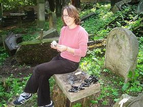 A volunteer from Germany sorting and cleaning shards from a headstone