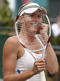 Nicole Vaidišová smiles through her racquet, after defeating Australia's Casey Dellacqua, in their Women's Singles, third round match at Wimbledon, photo: CTK