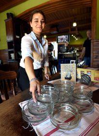 Servírka odklízí popelníky ze stolů, foto: ČTK