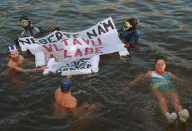 S transparentem Neberte nám Vltavu aLabe plavali 10. prosince ve Vltavě tři otužilci adva potápěči při protestní akci sdružení Arnika, foto: ČTK