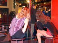 Na fotografii pořízené skrze sklo výkladu sledují ženy policejní razii v nočním klubu v Dubí na Teplicku, foto: ČTK