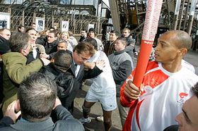 Security men tackle Green Party activist Sylvain Garel, third left at rear, as he tries to approach Stephane Diagana, right, the 400-meter world champion in 1997, as he carries the Olympic torch at the beginning of its relay from the first floor of the Eiffel tower in Paris, photo: CTK