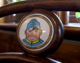 Josef Lada's depiction of Švejk on chair in a pub commemorating Švejk, photo: Mohylek, CC 3.0