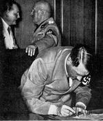 Adolf Hitler signs the Munich Agreement