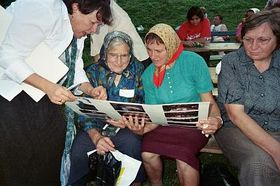 People at the festival reading greetings to them from people in Virginia, written on a poster-sized greeting card OR signing a poster-sized greeting card for us to take back to Virginia.